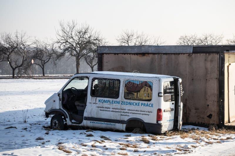 De beschadigde witte die bestelwagen van Renault Traffic dichtbij garages wordt verlaten die de omgeving verontreinigen royalty-vrije stock fotografie