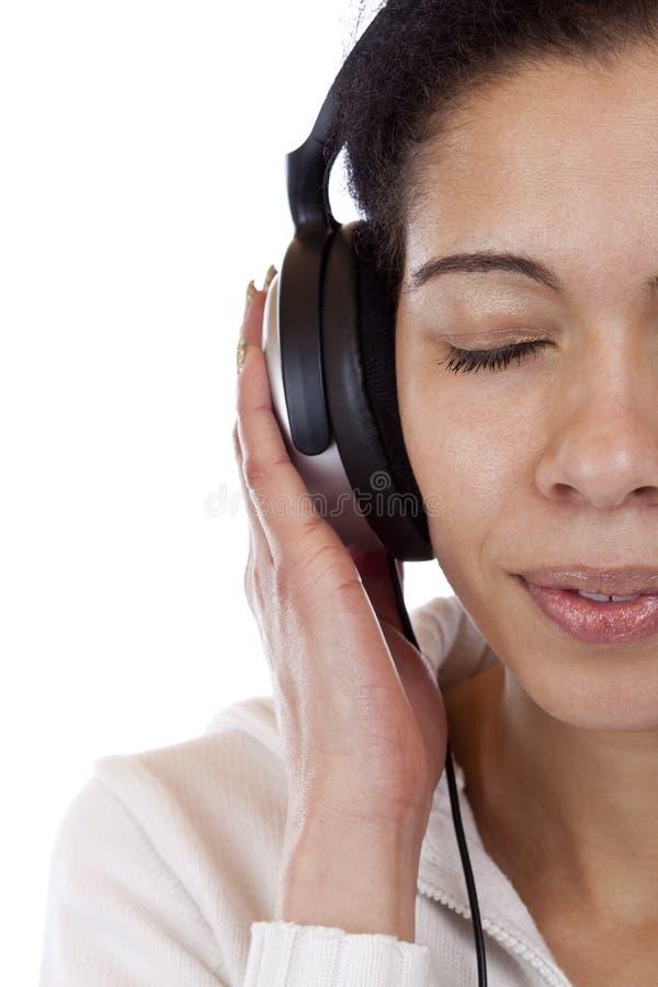 De besnoeiing van het gezicht van een vrouw die aan mp3 muziek luistert royalty-vrije stock foto