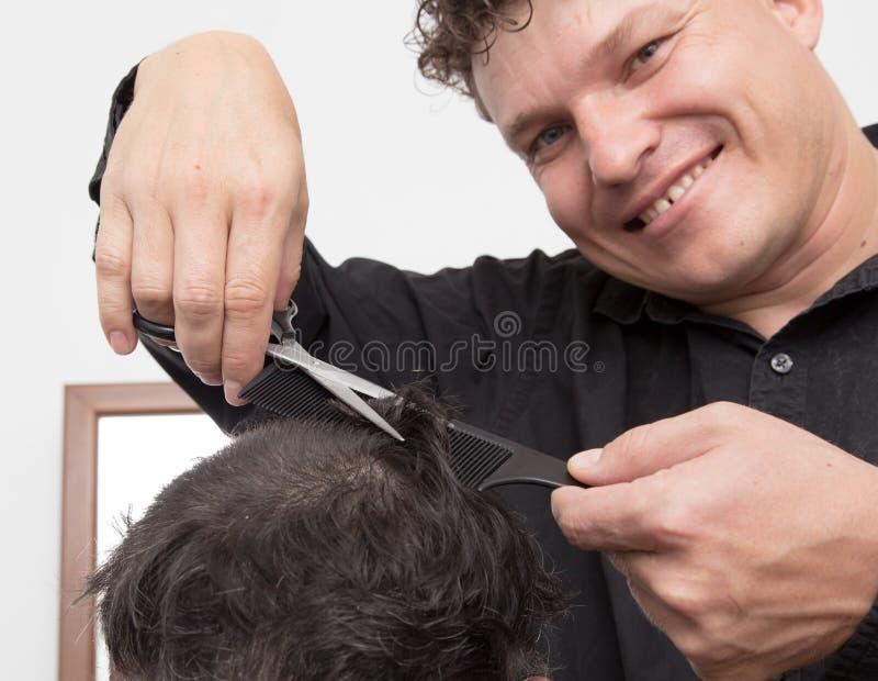De besnoeiing van het de mensen` s haar van kapperbesnoeiingen stock foto's