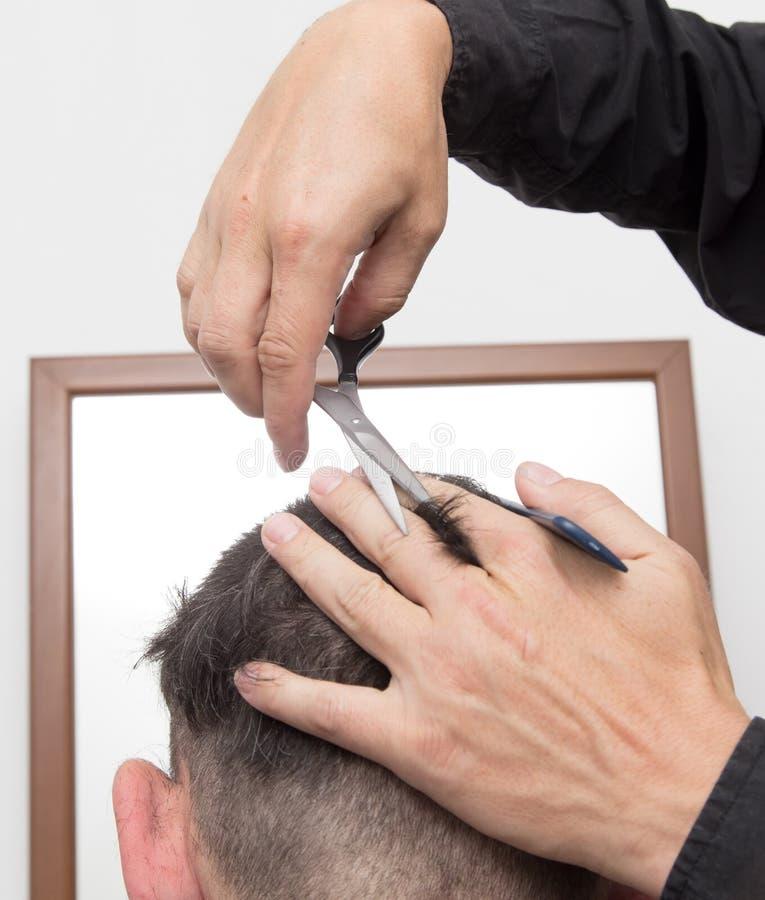 De besnoeiing van het de mensen` s haar van kapperbesnoeiingen stock fotografie