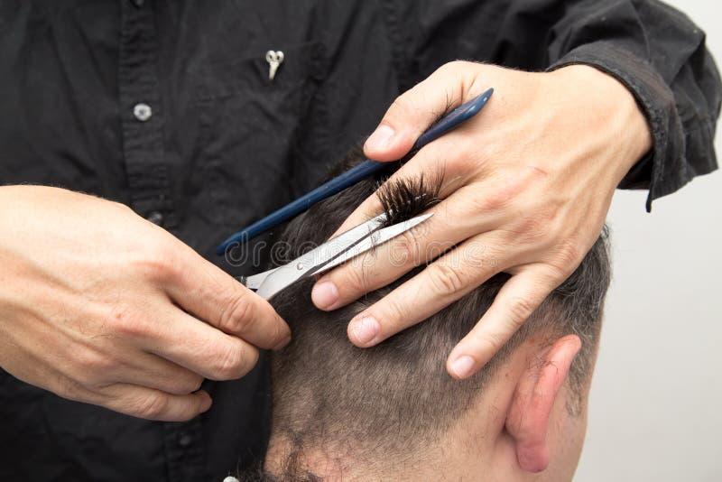 De besnoeiing van het de mensen` s haar van kapperbesnoeiingen stock foto