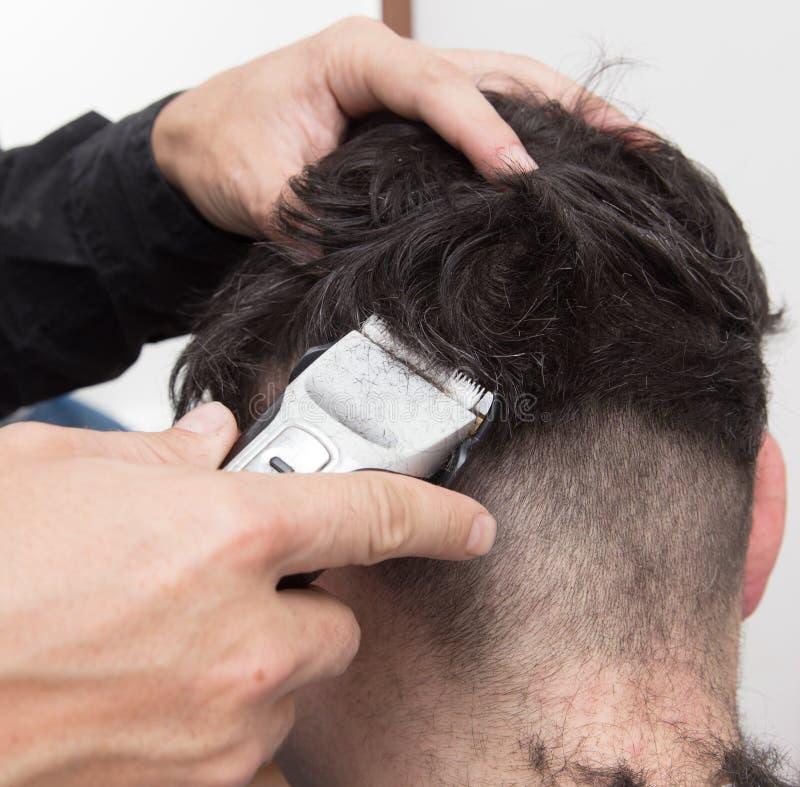 De besnoeiing van het de mensen` s haar van kapperbesnoeiingen stock afbeeldingen