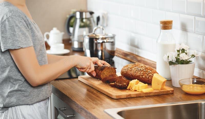De besnoeiingsbrood en kaas van handenvrouwen voor ontbijt stock foto's