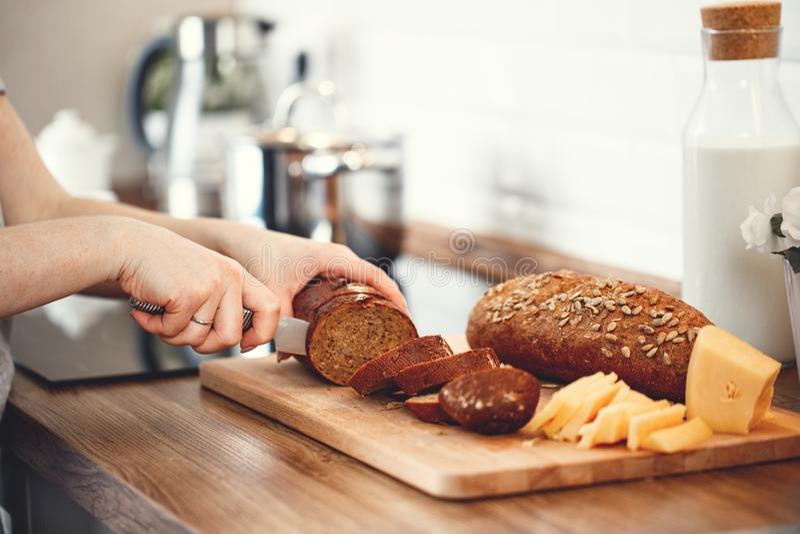 De besnoeiingsbrood en kaas van handenvrouwen voor ontbijt royalty-vrije stock fotografie