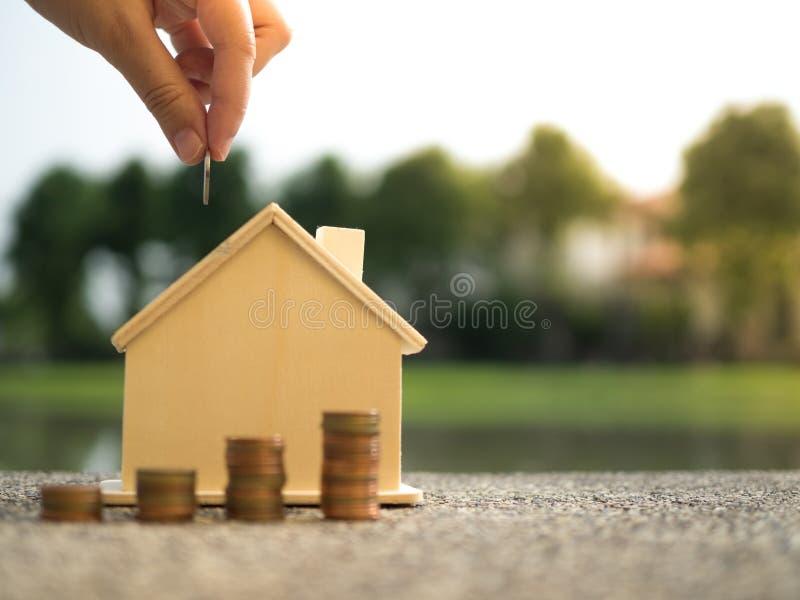 De besparing om een huis te kopen die dat overhandigt geldmuntstukken zetten stapelt het groeien, bewarend geld of van de geldgro stock afbeelding
