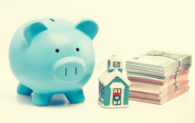 De besparingen van de onroerende goederenverkoop, leningenmarkt Het huis van het spaarvarken en stapel van euro contant geld stock afbeeldingen