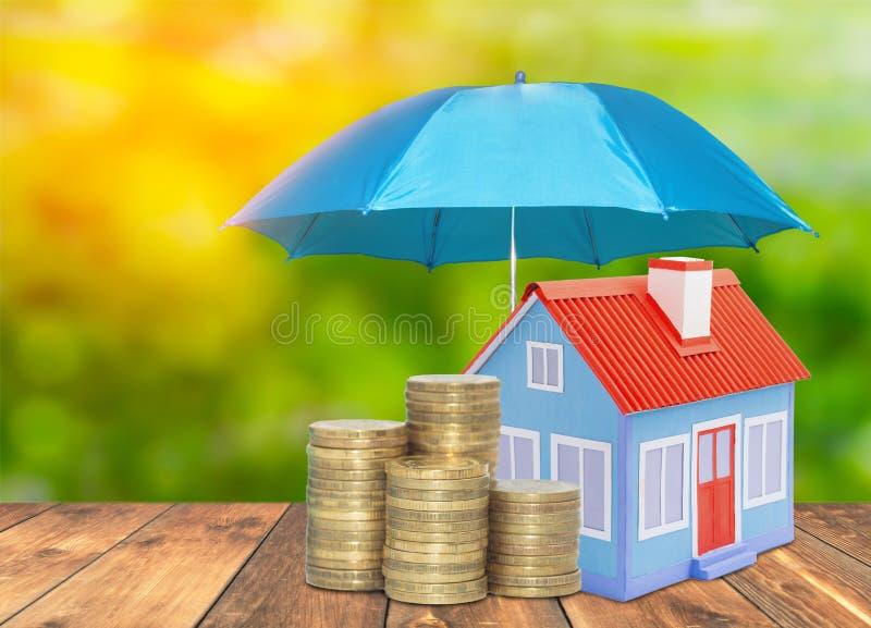 De besparingen van het Huismuntstukken van de paraplubescherming zaken Het concept van het de verzekeringshuis van het beschermin stock fotografie