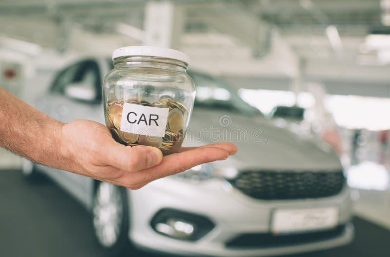 De besparingen verzamelen geld om een auto te kopen Gouden muntstukken in een glasflessen, die geld besparen om een autoconcept t stock fotografie