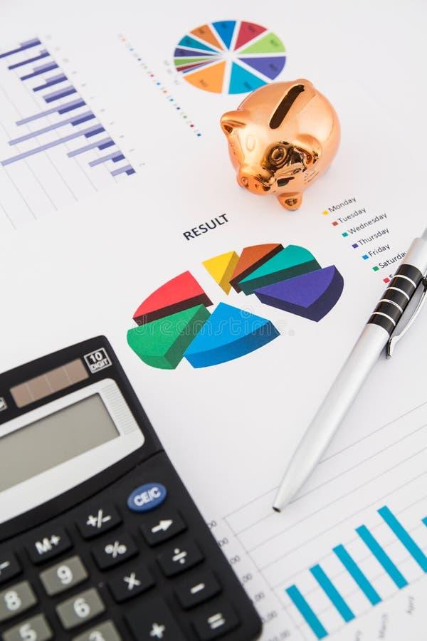 De besparingenconcept van het geld: grafieken, calculator, pen, varken. stock afbeeldingen