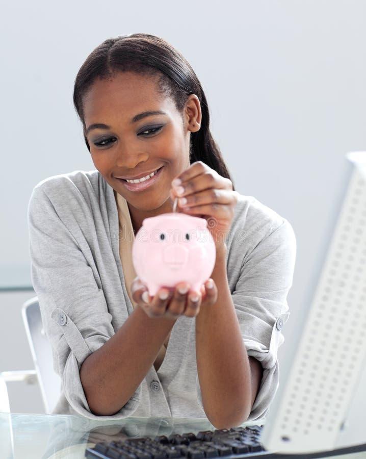 De besparingsgeld van de onderneemster in piggyban stock afbeeldingen