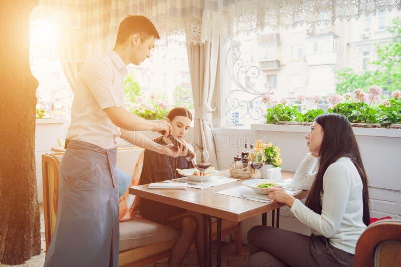 De bespreking van Nice kok vertellen vrouwelijke gasten over de schotel hij dient stock afbeeldingen