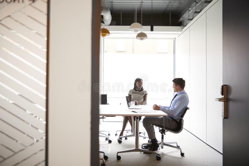 De Bespreking van zakenmanand businesswoman having rond Bestuurskamerlijst door Vergaderzaaldeur die wordt bekeken stock foto
