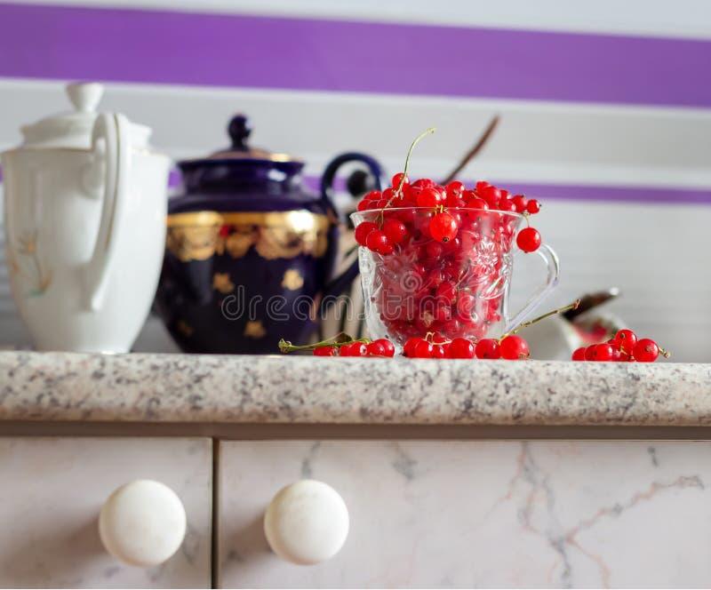 De bessen van de stillevenrode aalbes in glas overvallen op lijst en Twee uitstekende theepotten op witte lijst Selectieve nadruk stock afbeelding