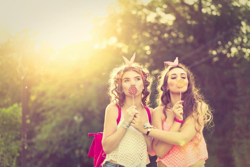 De beste meisjes verbergen lippen achter lollys Zonsondergang royalty-vrije stock afbeelding