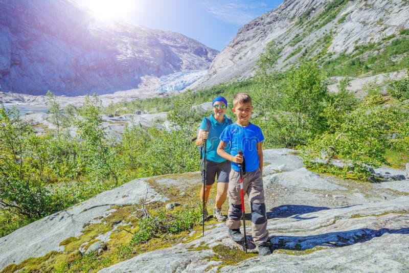 De beste stijging van Noorwegen Leuke jongen en zijn moeder met wandelingsmateriaal in de bergen stock fotografie