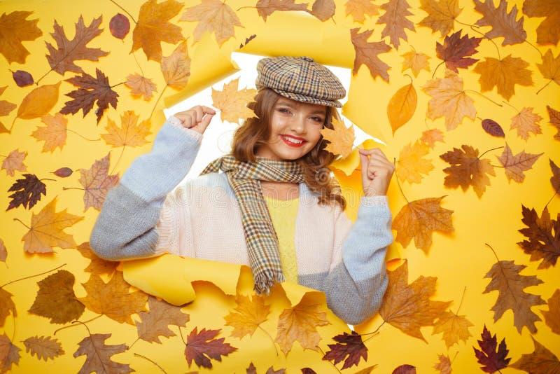 De beste stijl en de vorm Het maniermeisje kijkt door gescheurd document met de herfstbladeren Toevallige modetrends voor daling stock afbeeldingen