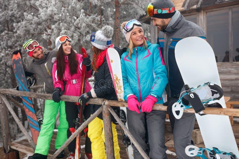 De beste vrienden besteden de wintervakantie bij bergplattelandshuisje stock afbeeldingen