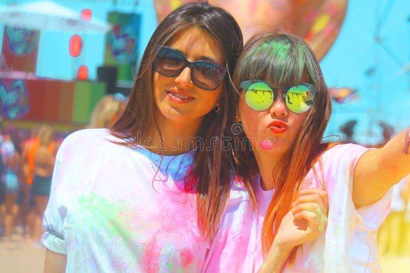 De beste vrienden bij holifestival twee meisjes die pret hebben kleurden met holipoeder royalty-vrije stock afbeeldingen
