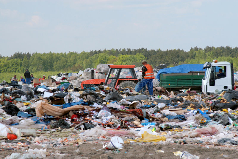 De bestelwagen van het afval op het dumpen grondgarbages stock fotografie
