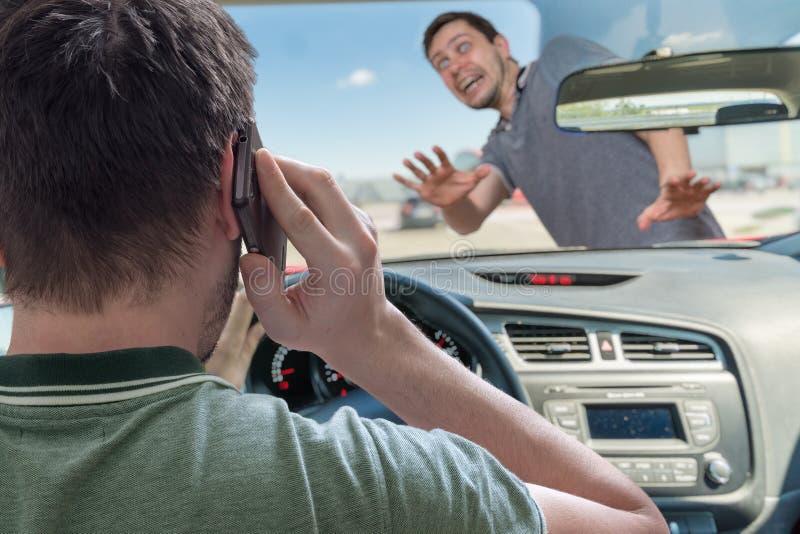 De bestuurder die het gebruiken van smartphone in auto roepen gaat voetganger raken stock foto's