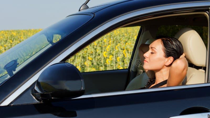 De bestuurder die van de vrouw achter het stuurwiel rust royalty-vrije stock foto