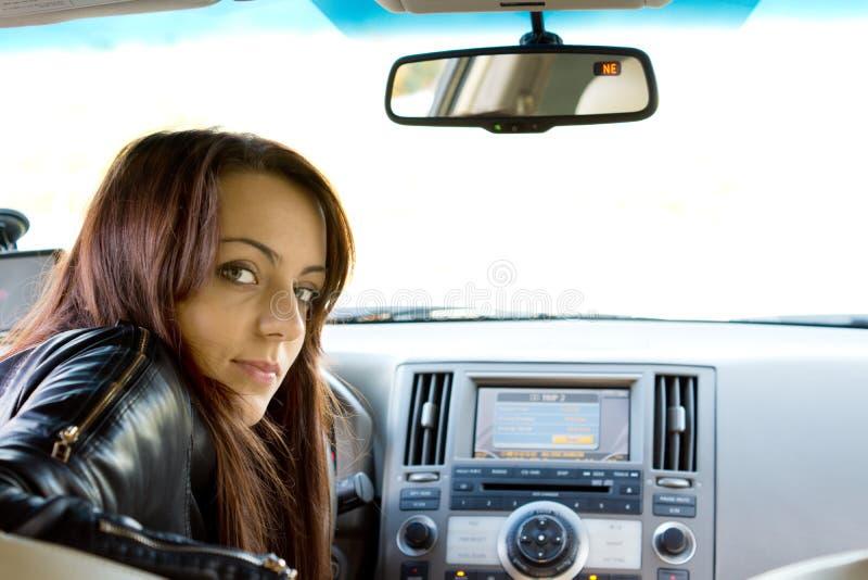 De bestuurder die van de vrouw de achterzetel onderzoekt stock foto's