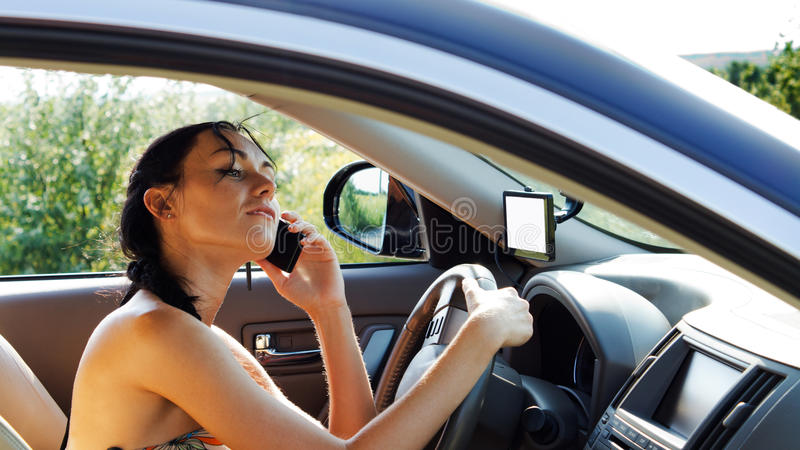 De bestuurder die van de vrouw mobiele telefoon met behulp van royalty-vrije stock afbeelding