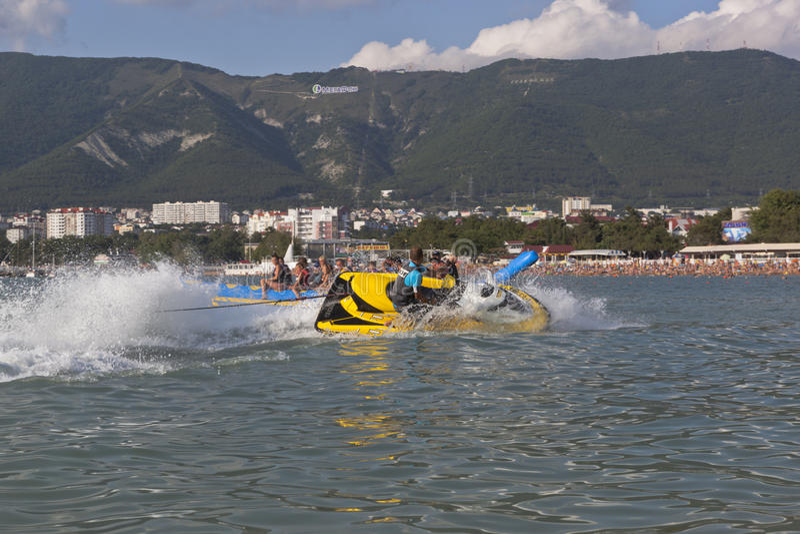 De bestuurder een watermotorfiets legt de steile draai en bestrooit water van passagiers opblaasbare banaan Gelendzhik royalty-vrije stock fotografie