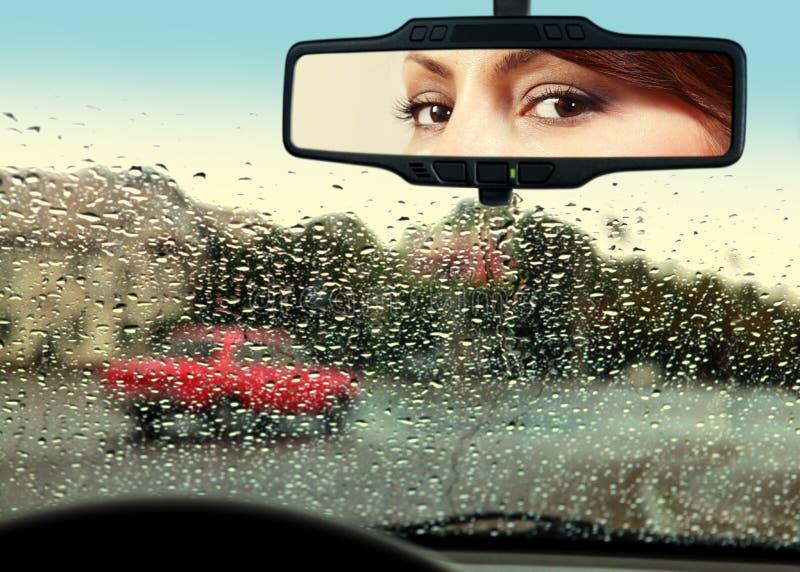 De bestuurder kijkt aan achteruitkijkspiegel royalty-vrije stock afbeelding