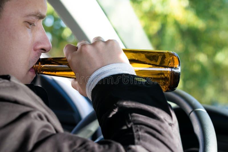 De bestuurder van de auto drinkt alcoholische dranken achter het wiel royalty-vrije stock fotografie