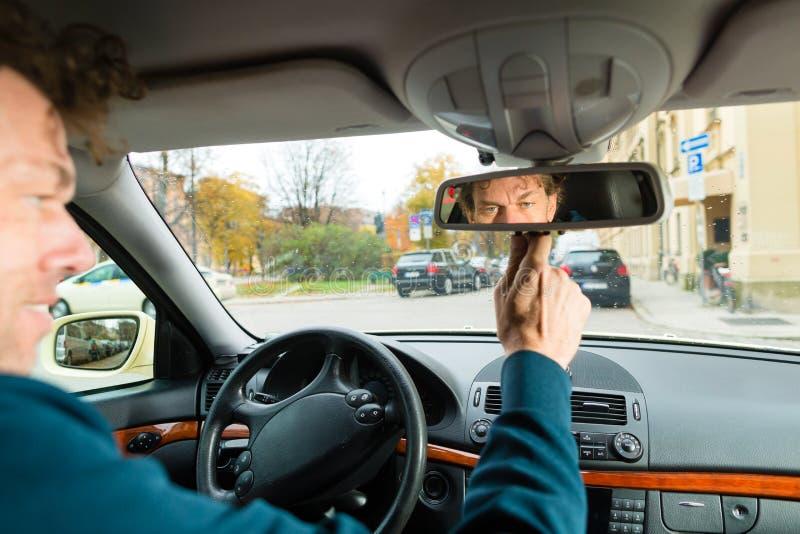 De bestuurder van de taxi kijkt in de drijfspiegel royalty-vrije stock afbeelding