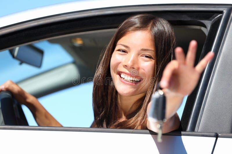 De bestuurder van de vrouw in auto die sleutels toont stock afbeeldingen