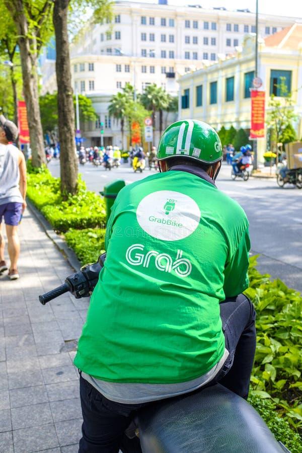 De bestuurder van de greepfiets in Saigon stock foto
