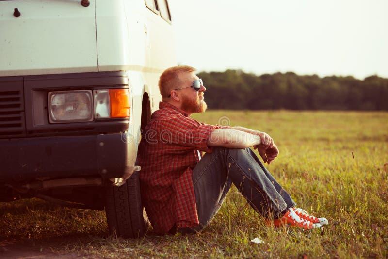 De bestuurder zit naast zijn auto royalty-vrije stock foto