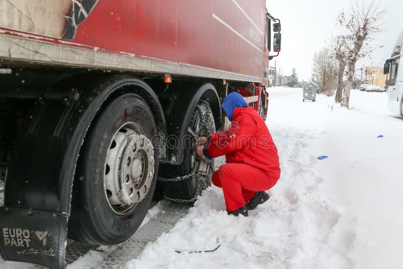 De bestuurders proberen om kettingen op hun banden onder zwaar te installeren