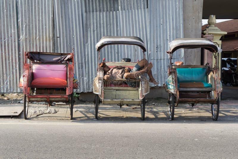 De bestuurders van mensenbecak wachten in slaap op de Klant op zijn riksja te vallen stock foto's