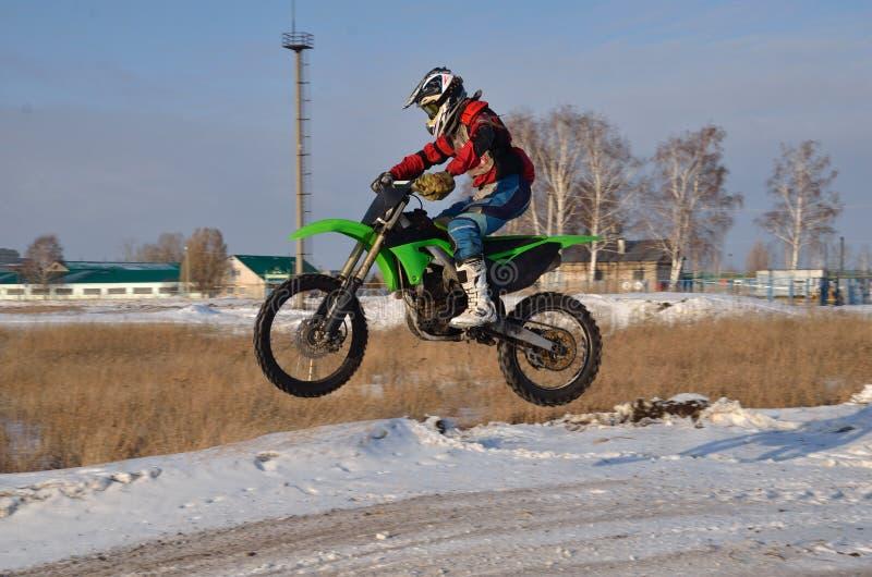 De bestuurdersvliegen van de motorfiets over heuvel uit sneeuw royalty-vrije stock afbeeldingen