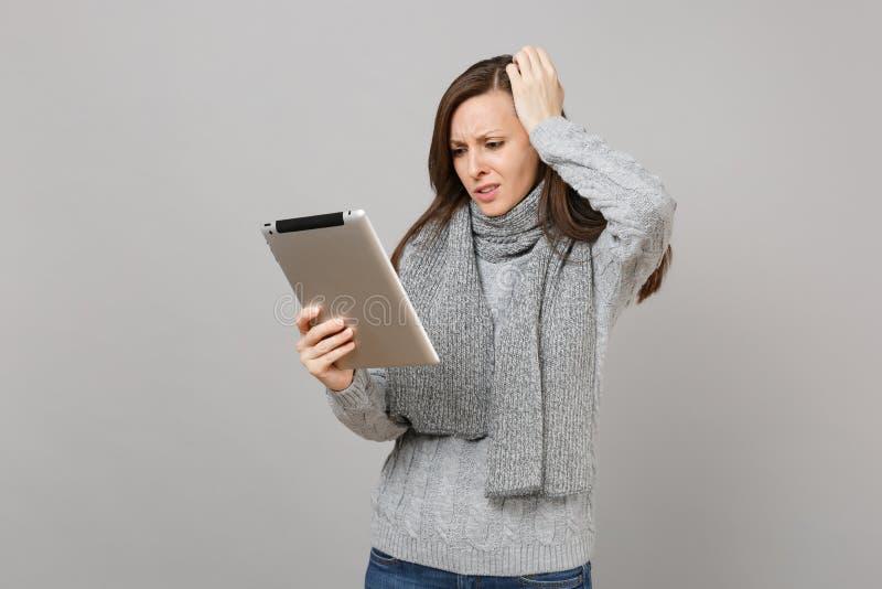 De betrokken jonge die vrouw in sweater, sjaal zette hand op hoofd, gebruikend de computer van tabletpc op grijze achtergrond wor royalty-vrije stock afbeelding