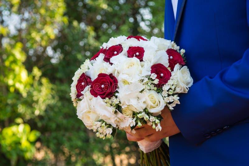 De bevindende bruidegom houdt mooi boeket van bloemen terwijl het wachten van de bruid stock foto
