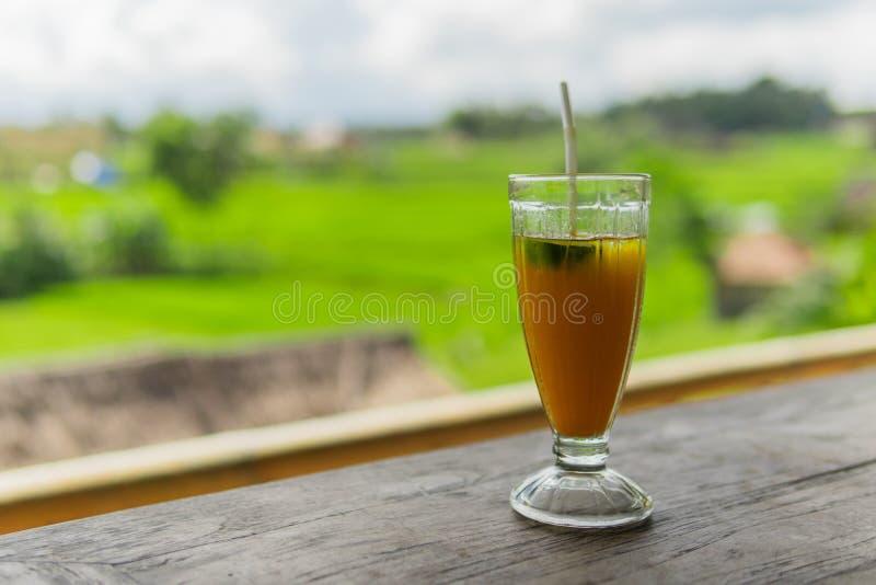 De bevroren drank van de mangopapaja banaan met padievelden op de achtergrond stock fotografie