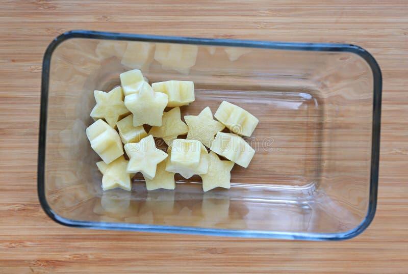 De bevroren eigengemaakte, gele ster van het babyvoedsel van slakubussen in vierkante glaskom op houten raad stock afbeelding