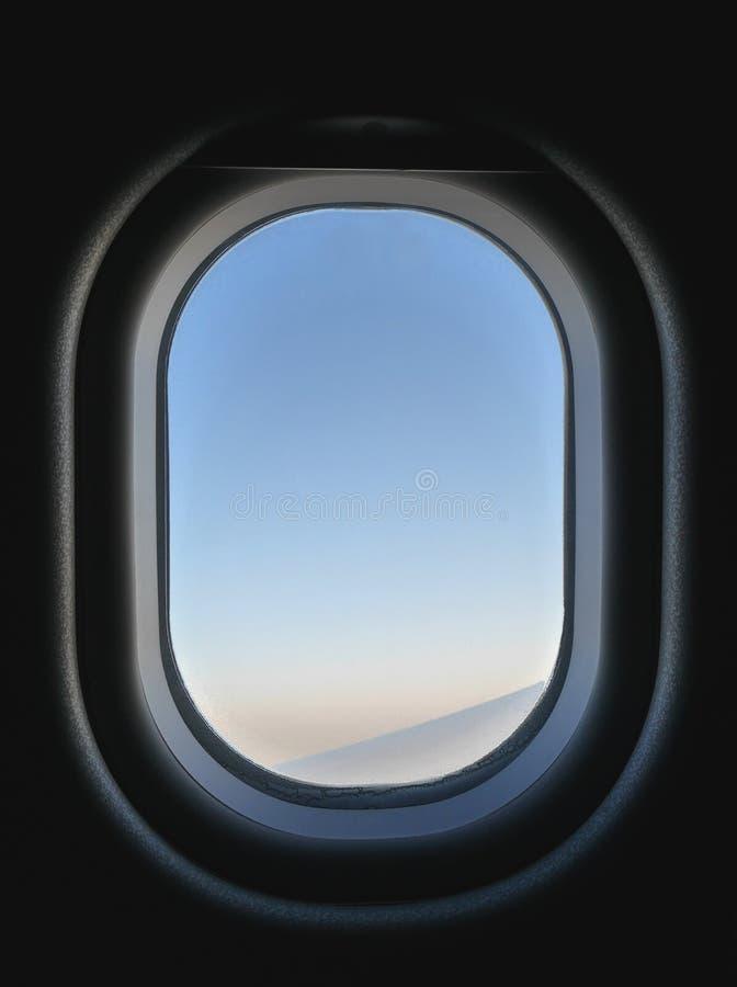 De bevroren mening van het vliegtuigvenster van binnenuit, ziend blauw en roze hemel en deel van vliegtuigen` s vleugel stock fotografie