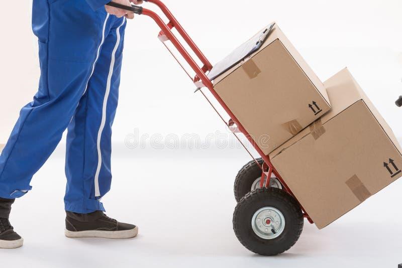 De bewegende pakketten van de leveringsmens met dolly royalty-vrije stock afbeelding