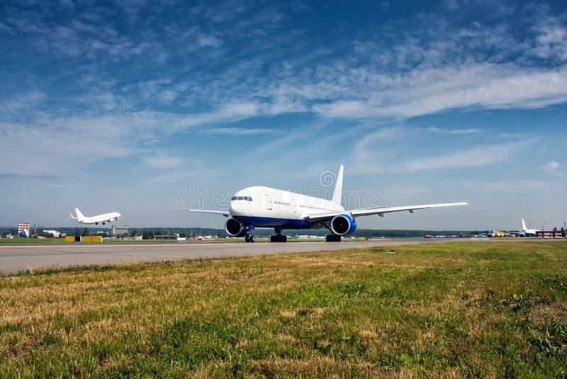 De bewegingen van het passagiersvliegtuig op de belangrijkste taxibaan en achter vliegtuig gaat van start stock afbeeldingen