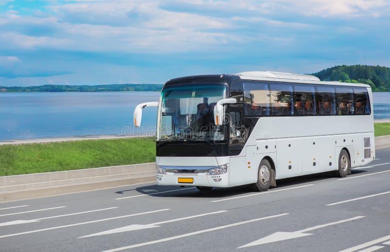 De bewegingen van de toeristenbus langs de weg langs de meerkust stock fotografie