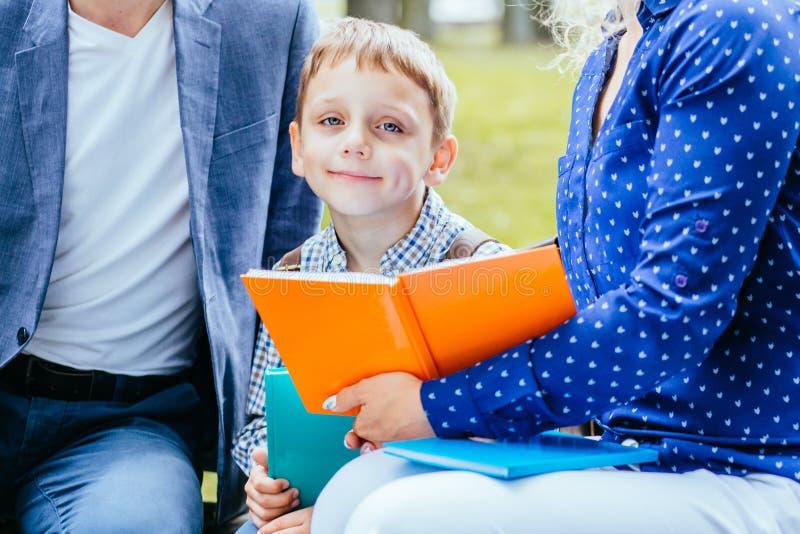De bezette zitting van de kindjongen tussen moeder en vader en lezings interessant boek openlucht royalty-vrije stock foto's