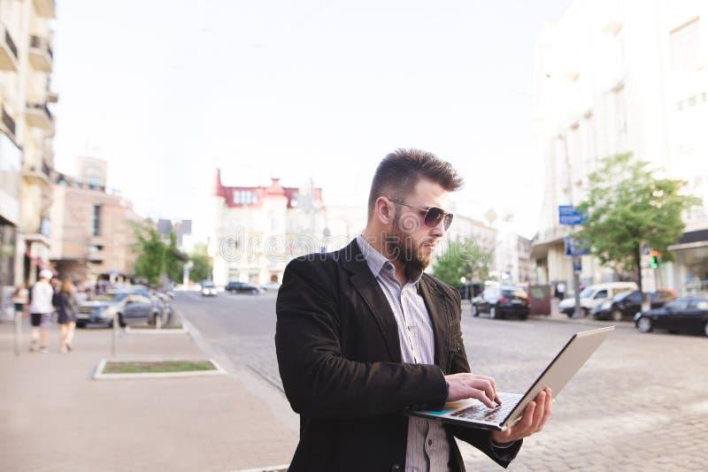 De bezige bedrijfsmens bevindt zich in de straat met laptop in zijn handen en werken stock afbeeldingen