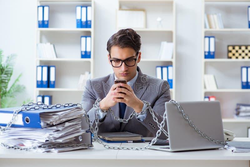 De bezige die werknemer aan zijn bureau wordt geketend royalty-vrije stock fotografie