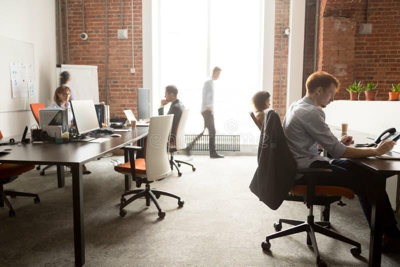 De bezige groep die van personeelswerknemers aan computers in bureaustormloop werken stock fotografie