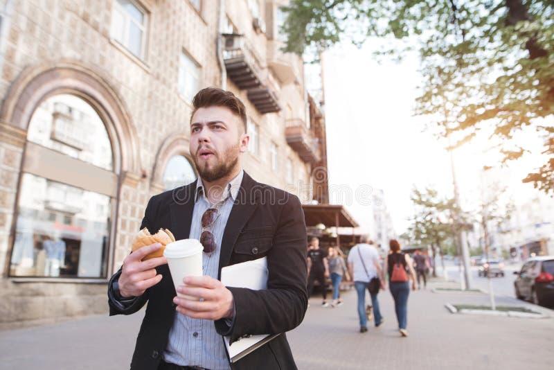 De bezige mens eet en drinkt koffie terwijl het lopen voor het werk De bedrijfsmens heeft ontbijt met snel voedsel stock afbeelding